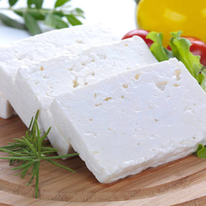 """feta cheese cut in slices, vegetables, herbs and olive oil-the ingredients for a greek salad"""